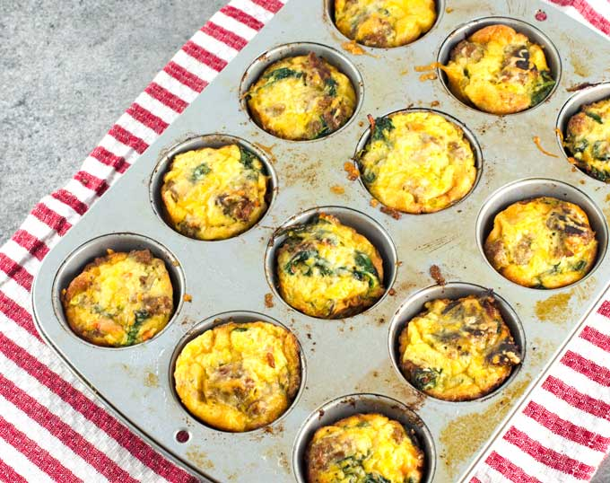baked frittatas cooling in the muffin tin on a white and red striped towel on a dark gray surface