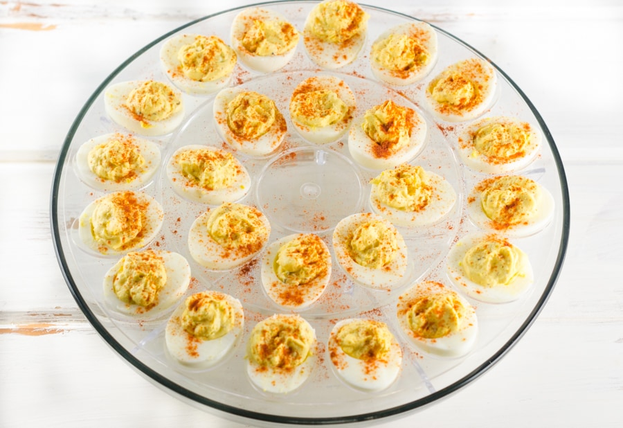 A fill deviled egg platter on a distressed white wood table top