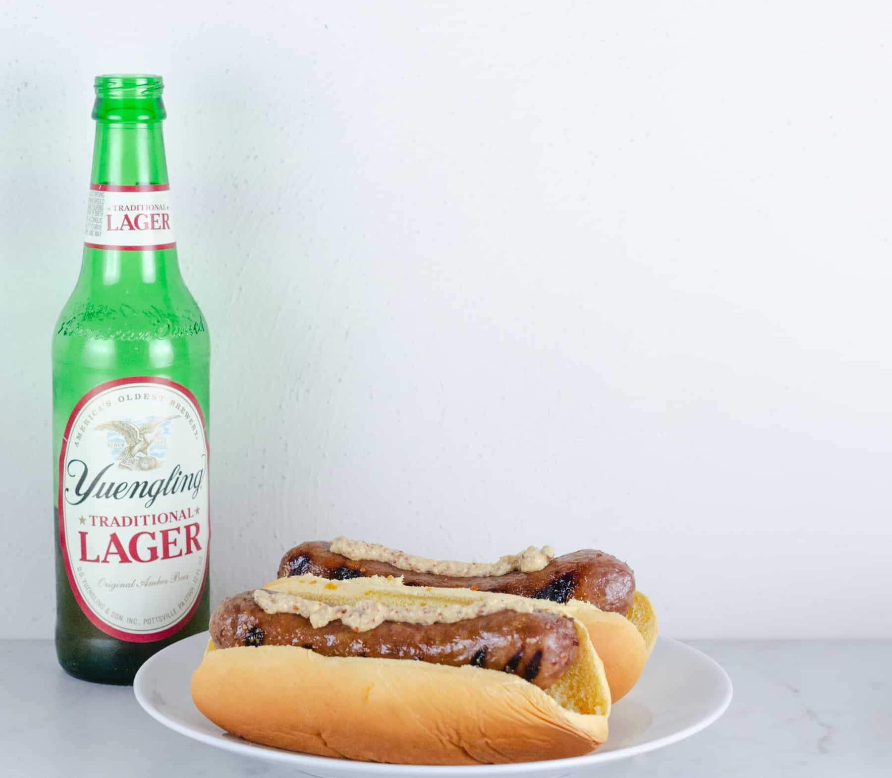 Honey Mustard Beer Glazed Bratwurst Recipe photo - brats in buns on a plate paired with yuengling lager in a bottle